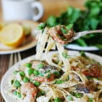Healthy fettuccine alfredo with cauliflower sauce, shrimp, mushrooms, and sweet peas