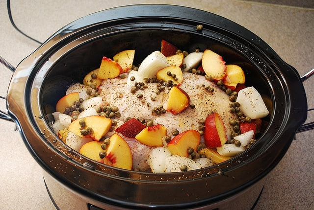 slow cooker raw whole chicken topped with peaches and capers
