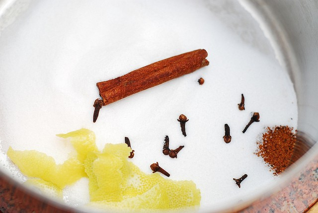 placing sugar spices and lemon peel in the pan