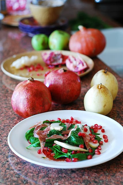 Spinach salad with pomegranate seeds, pears, and prosciutto