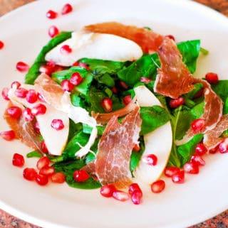 Spinach salad with prosciutto, pears, pomegranate
