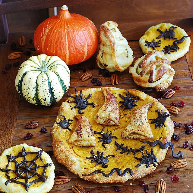 Nightmare harvest: Halloween pumpkin puff pastry pie (tart) with apple-cranberry stuffed crust, chocolate bugs, and cinnamon wizard hats