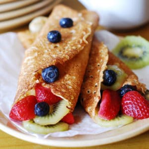 Homemade dessert crepes with ricotta cheese filling, berries, and kiwi