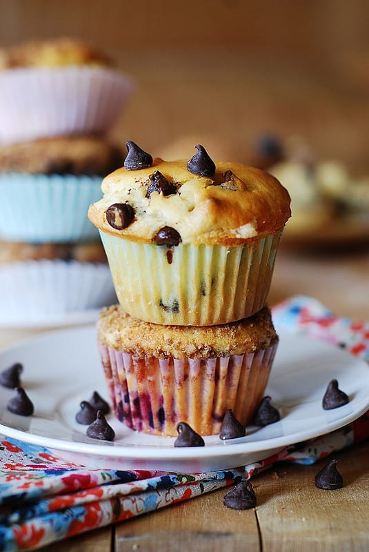 Greek yogurt chocolate chip muffins on a plate with chocolate chips scattered around