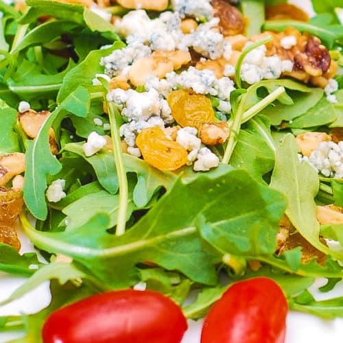 arugula salad with walnuts, raisins, gorgonzola, grape tomatoes with honey balsamic dressing