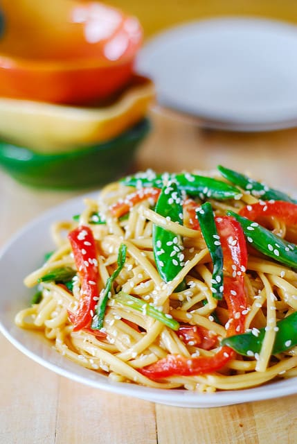 Cold Asian noodle salad recipe with snap peas and red bell peppers topped with toasted sesame seeds