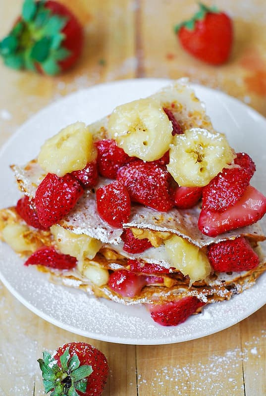 folding each crepe to form a triangle, then topping with more fruit and berries