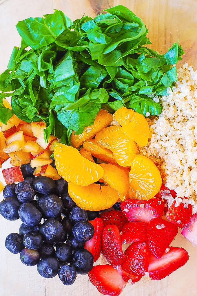 Quinoa salad with spinach, strawberries, blueberries, peaches, mandarin oranges