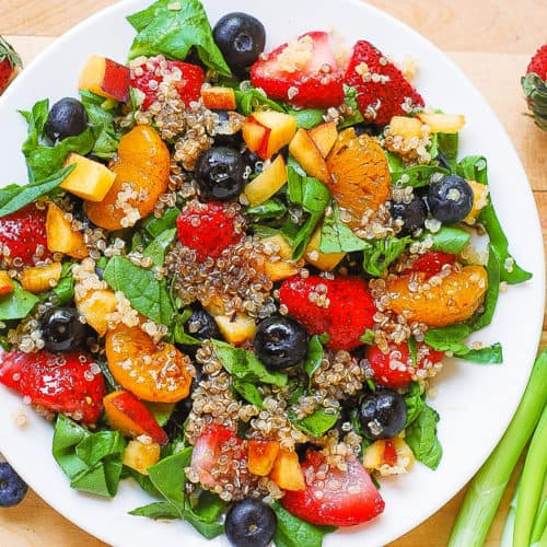 Quinoa salad with spinach, strawberries, blueberries, peaches, mandarin oranges in a homemade Balsamic vinaigrette dressing on a white plate
