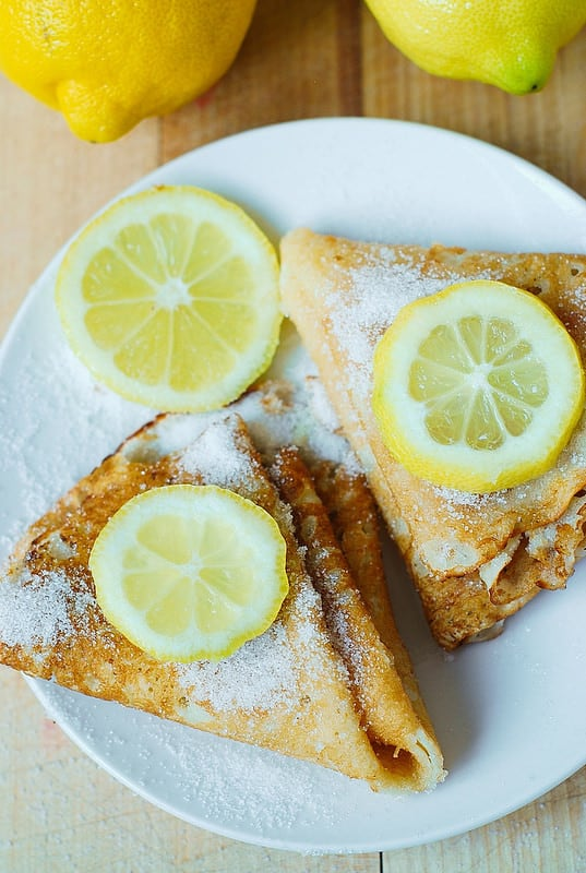 Homemade blini sprinkled with sugar and lemon slices on top