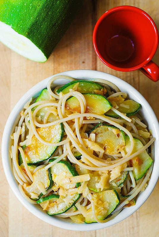 Parmesan Zucchini & Garlic Pasta in a white bowl with a red cup and a whole zucchini