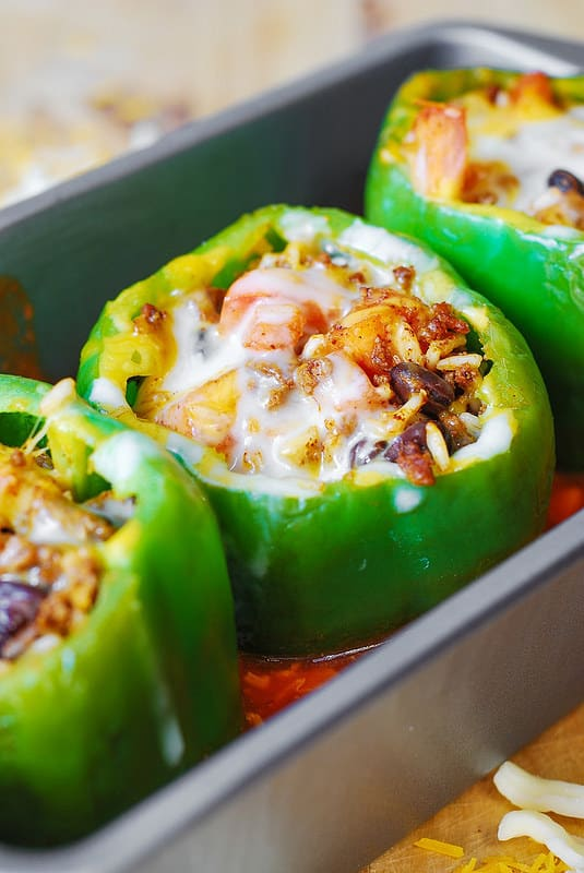 Stuffed bell peppers with ground beef black beans tomatoes and rice and cheese