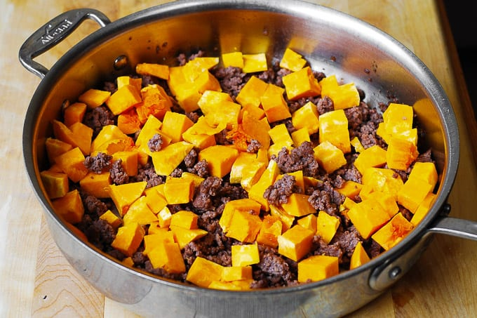 Adding cubed butternut squash to the skillet with cooked ground beef