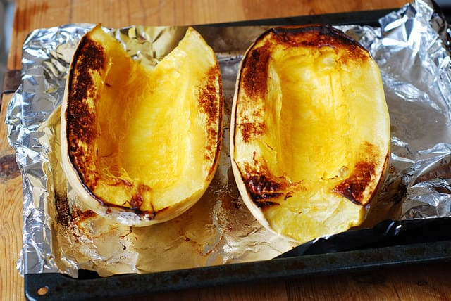 two halves of spaghetti squash on a baking sheet after roasting