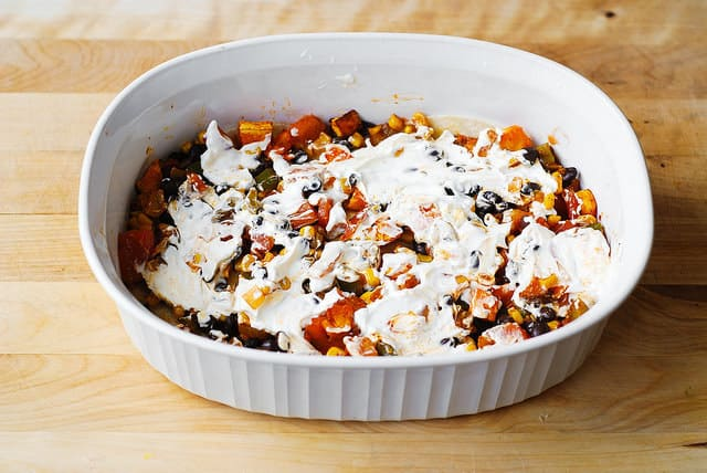 Spread sour cream over the roasted vegetables