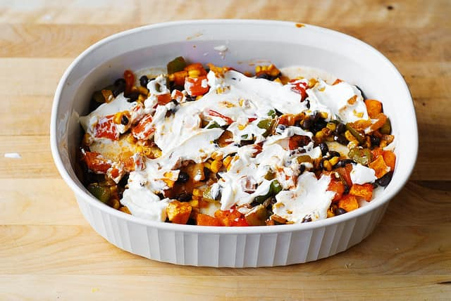 Spread sour cream over the veggies in a casserole dish