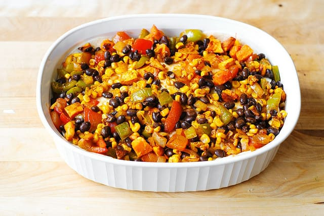 Spread the veggies on top: butternut squash, black beans, red bell peppers, green bell peppers, corn, black beans - Mexican enchilada casserole dish