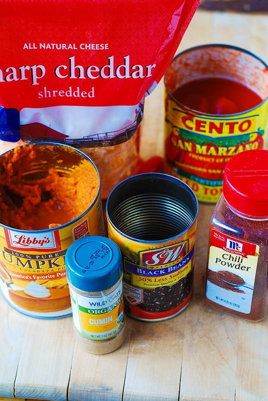 Pumpkin and beef chili ingredients: canned peeled tomatoes, sharp cheddar shredded cheese, canned pumpkin, canned black beans, chili powder, cumin powder