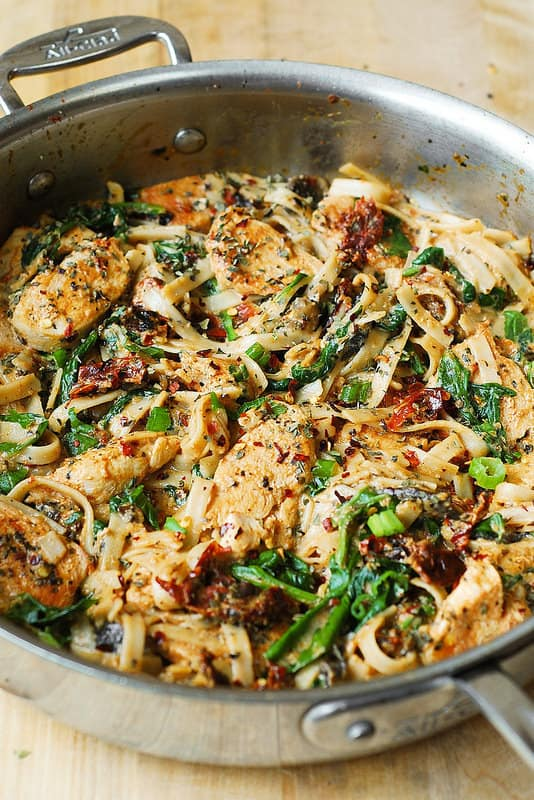 Chicken Pasta with Sun-Dried Tomatoes and Spinach in a Creamy Cauliflower Alfredo Sauce in a large All-Clad skillet