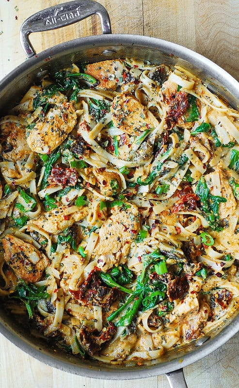 Chicken Pasta with Sun-Dried Tomatoes and Spinach in a Creamy Cauliflower Alfredo Sauce in all-clad skillet