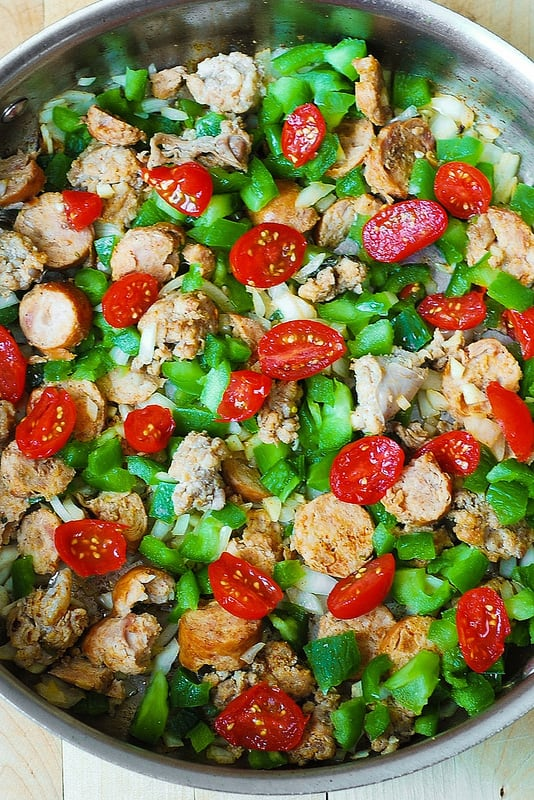 adding tomatoes to green bell peppers and sausage skillet