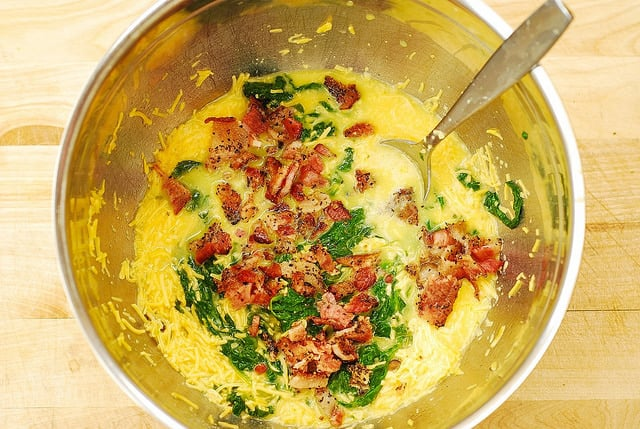 adding cooked bacon to spinach, eggs, cheddar cheese for egg muffins (process shot)