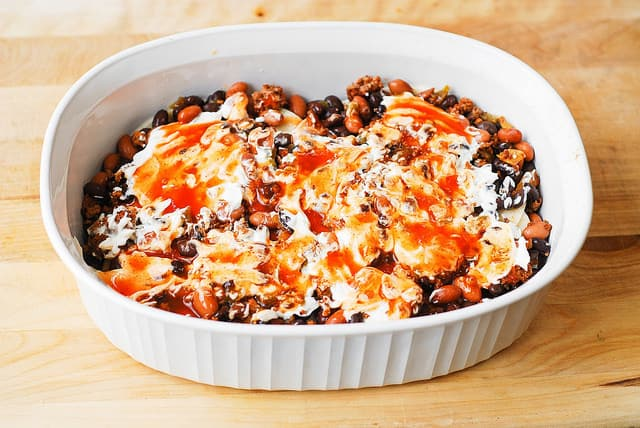 Top the mixture with enchilada sauce - spread enchilada sauce and sour cream over the beans and beef (enchilada casserole)
