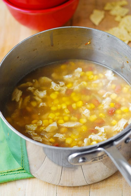 adding corn and refried pinto beans to the white chicken chili
