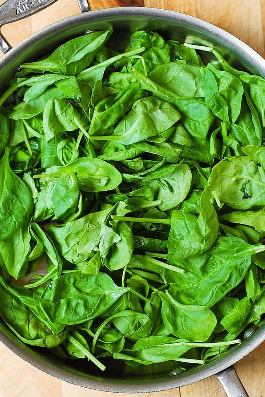 add fresh spinach to a large skillet with garlic