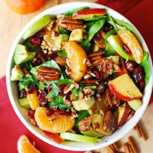 Apple Cranberry Spinach Salad with Pecans, Avocados, and Balsamic Vinaigrette Dressing in a white bowl