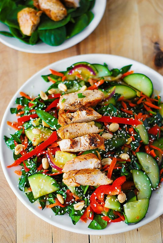 Crunchy Asian Salad with chicken, spinach, cucumbers, red bell pepper, carrots, sugar snap peas, toasted peanuts and sesame seeds, and homemade Sesame Peanut Dressing