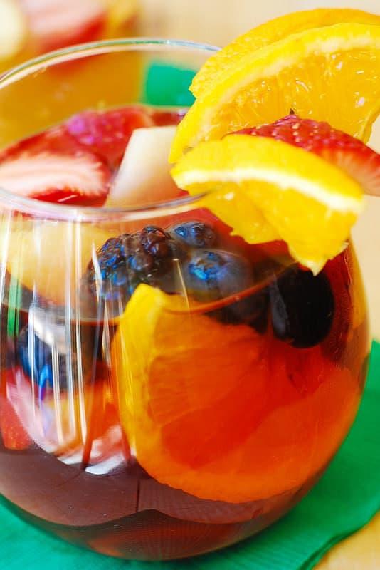Red Sangria with dry red wine, triple sec, brandy, lemon juice and orange juice, and with lots of berries and fruit: strawberries, blueberries, blackberries, oranges, and lemon