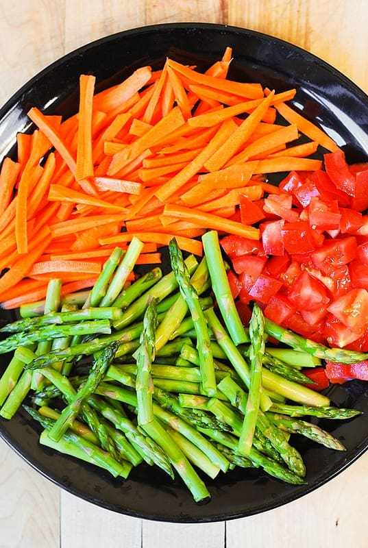 carrots, tomatoes, asparagus on a plate