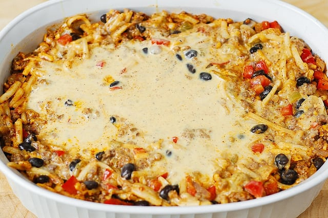 pouring egg mixture over Southwestern hash brown casserole in a casserole pan (step-by-step photos)