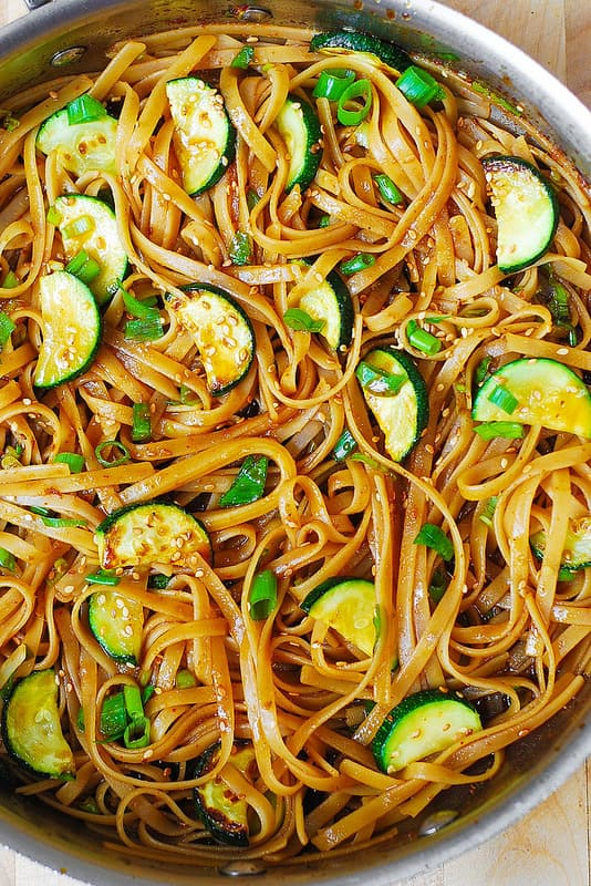 Thai zucchini noodles with red curry paste honey soy sauce and sesame seeds in a large skillet