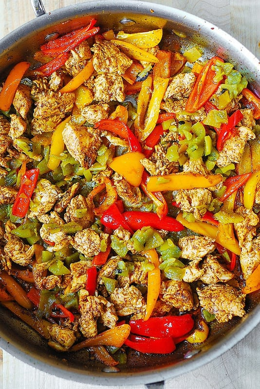 cooking chicken with bell peppers and green chiles in a large skillet (process shot)
