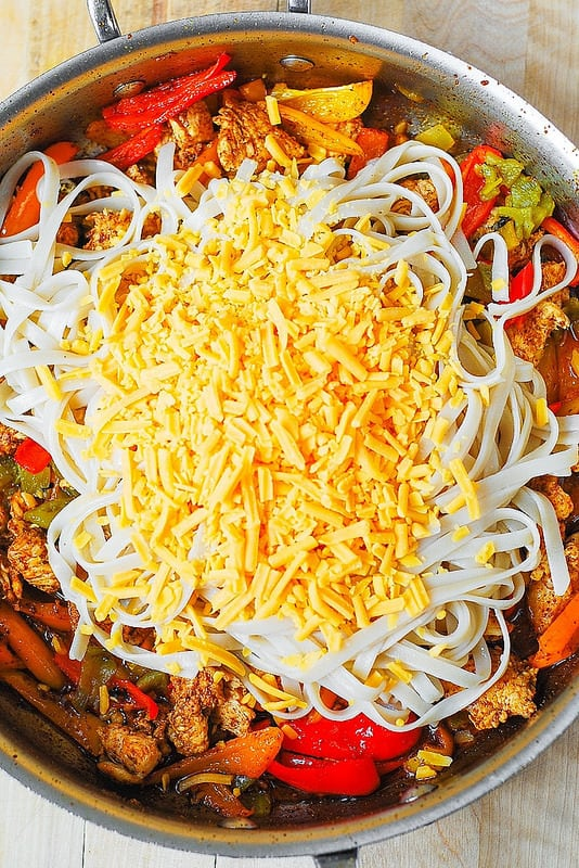 add pasta and Cheddar cheese to chicken, bell peppers, green chiles, Mexican spices to a large skillet (step-by-step photos)
