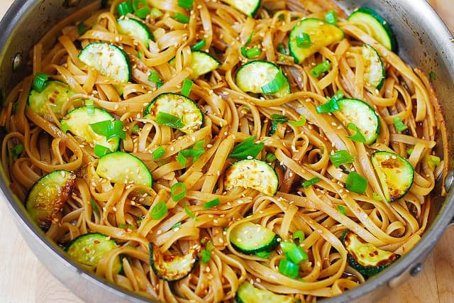 combining gluten free fettuccine noodles with zucchini in Thai Asian sauce (process shot)