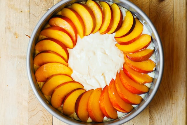adding cheesecake filling on top of the cake with sliced peaches (step-by-step photos)