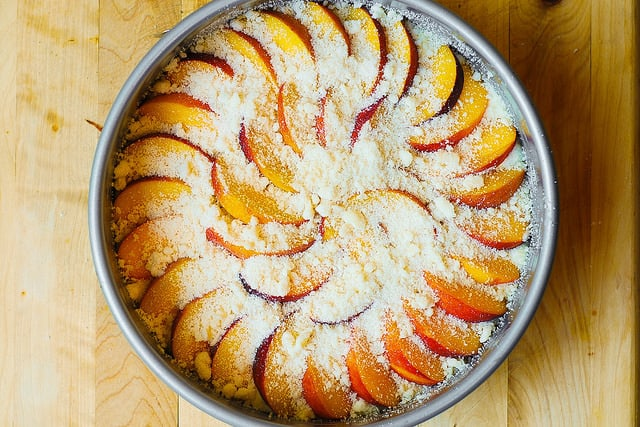 sprinkling streusel over the peaches on the cake (process shot)