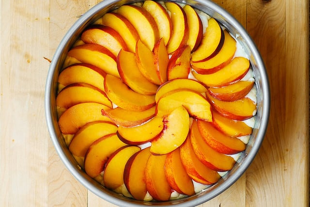adding sliced peaches in circles on top of the cake (process shot)