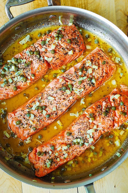 Steelhead Trout with Garlic Butter Lemon Caper Sauce in a skillet