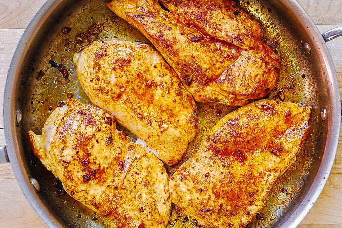 cooking chicken breasts with paprika in a skillet