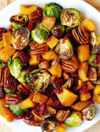 Roasted Butternut Squash and Brussels sprouts with Pecans and Dried Cranberries on a white plate