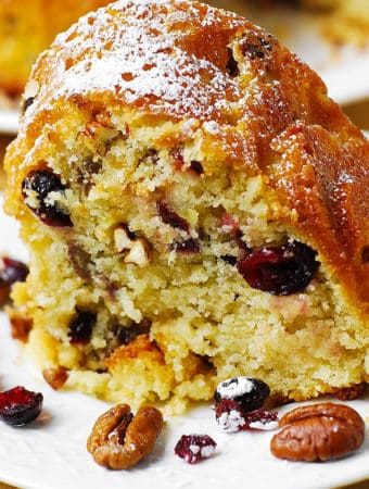 Buttermilk Bundt Cake with Cranberries, Apples, and Pecans on a white plate