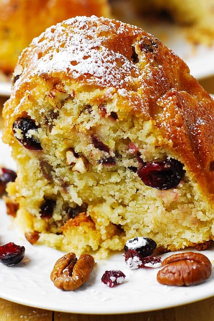 a slice of Buttermilk Bundt Cake with Cranberries, Apples, and Pecans on a white plate