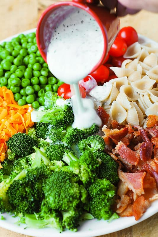 adding creamy Ranch dressing to Broccoli Bacon Ranch Pasta Salad with cherry tomatoes, sweet peas