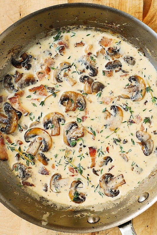 add heavy cream and thyme to the skillet with mushrooms and bacon to make the sauce (process shot)