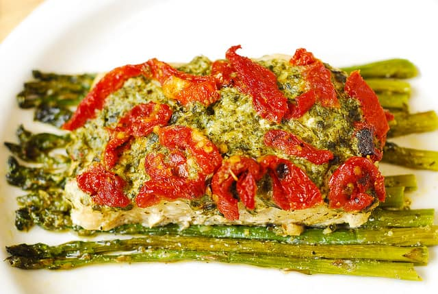 Baked Basil Pesto Sea Bass and Veggies (Asparagus and Sun-Dried Tomatoes) on a white plate