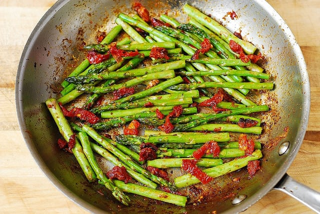 cook asparagus with sun-dried tomatoes in a skillet (process shot)